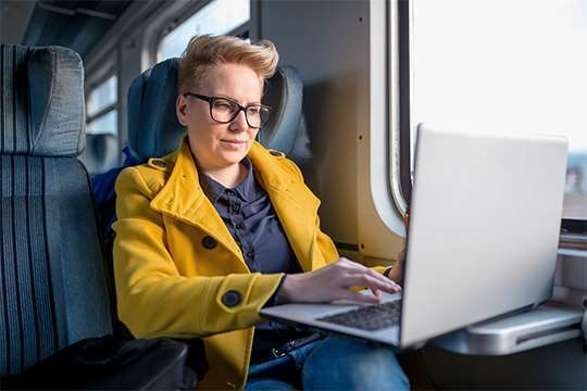 Business: Lady in train with laptop